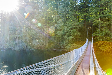 Sunshine lights the way along a suspension bridge across the end of Buntzen Lake trail to continue the path into the forest trails near Vancouver, British Columbia, Canada