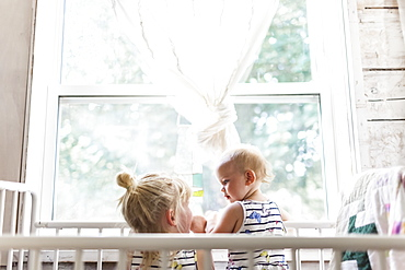 Two sisters, a baby and a toddler, play together in a crib by a window, Sorrento, British Columbia, Canada