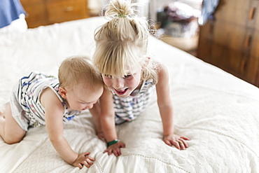 Two sisters, a baby and a toddler, play together on a bed, Sorrento, British Columbia, Canada