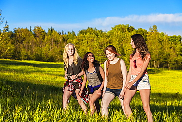 A group of four girlfriends hike together through a field in a park, Edmonton, Alberta, Canada