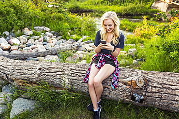 A young woman sits on log in a park using her cell phone with a river in the background, Edmonton, Alberta, Canada