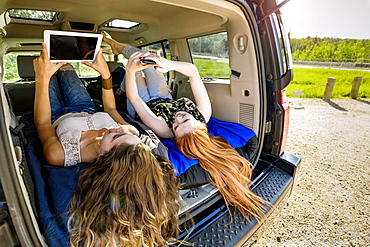 Two young women on a road trip sit in the back of a vehicle using a smart phone and tablet, Edmonton, Alberta, Canada