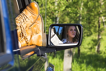A female passenger with her feet out the window of the vehicle during a rest stop on a road trip, Edmonton, Alberta, Canada