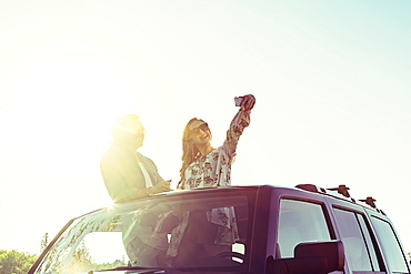 Young couple taking self-portraits with a cell phone while standing up in their sunroof of their vehicle, Edmonton, Alberta, Canada