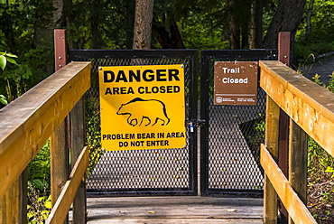Bear warning sign posted on a closed gate where a trail has been closed, Liard River Hot Springs Provincial Park, British Columbia, Canada