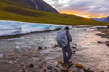 A backpacker observes the midnight sun peeking through the clouds from an unnamed fork of the Atigun River still partially covered in aufeis (sheet-like ice formations) in a remote valley of the Brooks Range, Alaska, United States of America
