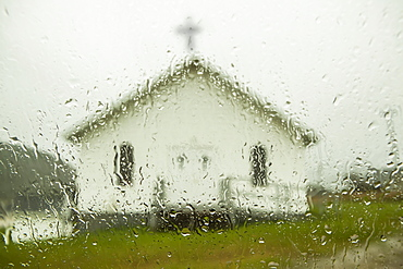 A white church building with cross viewed through a window wet with raindrops, Newfoundland, Canada