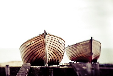 Two wooden boats sitting on the shore, England