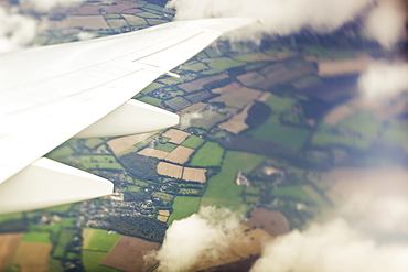 Aerial view of a patchwork landscape of farmland out the window of an airplane, Hastings, England