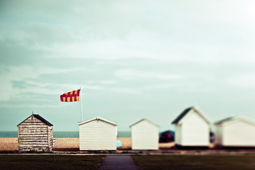 Small wooden buildings in a row on the beach with a view of the ocean, England
