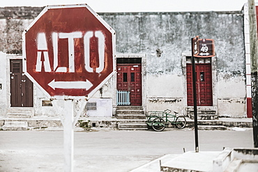 A stop sign with an arrow in Spanish along a street with houses in the background, Cancun, Mexico