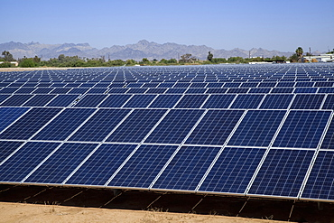 Close-up of solar panels with farm buildings and mountains beyond, near Blythe, California, United States of America
