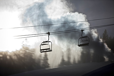 Silhouette of a chairlift on a ski hill with man made snow from snow gun backlit by the sunlight, Copper Mountain Resort, Colorado, United States of America