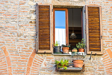 Close View Of A Montepulciano Brick House Facade With Opened Window, Flowerpots And Latticed Sun Blinds, Tuscany, Italy