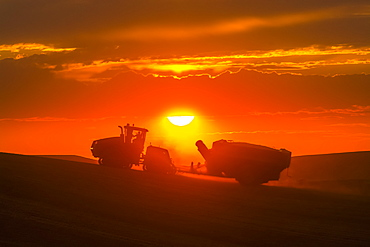 Case Quadtrac Tractor Pulling A Grain Cart In A Wheat Field During Harvest In The Palouse Region Of Eastern Washington, Washington, United States Of America