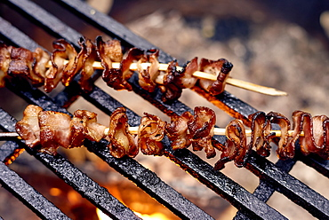 Bacon Skewers Cooking Over A Flame On A Grill, Ontario, Canada