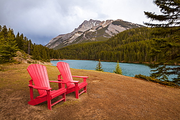 Two Red Adirondack Chairs On A Grassy Hill In Alberta's Mountains And Lakes, Alberta, Canada