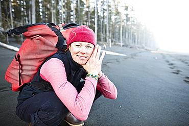 A Woman Crouching On The Beach Carrying A Backpack, Kenai Peninsula Outer Coast, Alaska, United States Of America