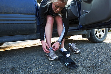 A Young Woman Sits On The Seat Of Her Car With The Door Open Changing Shoes Before Going For A Run, Homer, Alaska, United States Of America