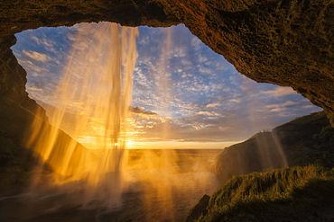 Sunset Light Shines Through The Water Of Seljandefoss Along The South Coast, Iceland