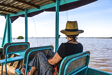 A Woman Sits On A Boat Looking Out At The Water As It Tours Down A River, Siem Reap Province, Cambodia