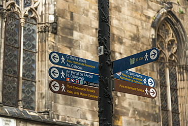 Destination Signs For Landmarks On A Post With An Old Stone Wall And Windows In The Background, Gothic Quarter, Barcelona, Catalonia, Spain