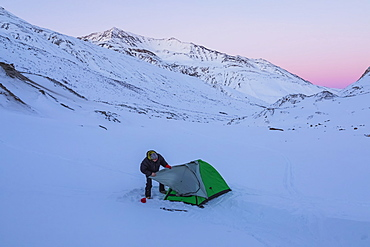 A Man Assembling A Tent After Sunset During A Winter Camping Trip In The Alaska Range, Near Augustana Glacier, Alaska, United States Of America