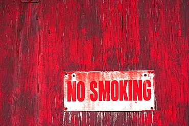 A No Smoking Sign On A Painted Red Wooden Wall, Orion, Alberta, Canada