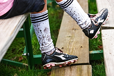 A Soccer Player Sitting On Wooden Stands Wearing Cleats And Mud Splashed Socks, Oregon, United States Of America