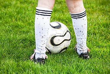 A Soccer Player Standing On A Grass Field With A Soccer Ball And Mud Splashed Socks, Oregon, United States Of America
