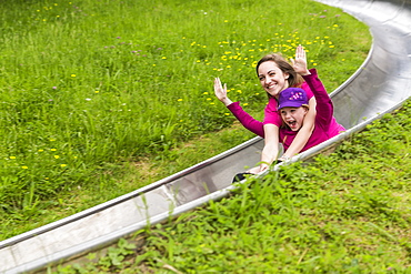 Two Smiling Teenage Girls Slide Down A Bobsled Track Embracing Each Other, Arms Raised In Joy, North Rhein, Westphalia, Germany