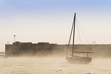 Wind Blows Sand Up On The Beach Against A Sailboat Sitting On The Shore, Lindisfarne, Northumberland, England