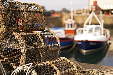 Traps Sitting On The Shore With Fishing Boats Moored In The Background, St. Abbs Head, Scottish Borders, Scotland