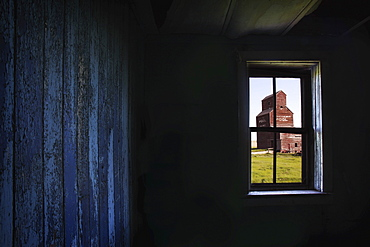 A Grain Elevator Seen Through The Window Of An Old, Abandoned Ghost Town Store; Bents, Saskatchewan, Canada