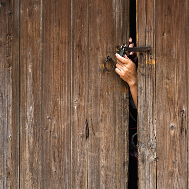 A hand reaching out a wooden door to unlock a padlock