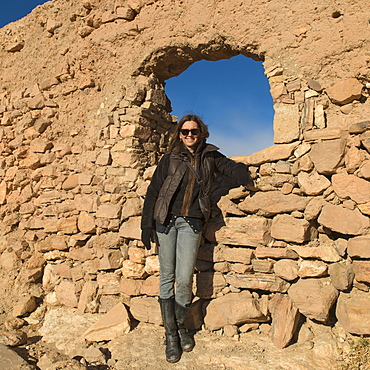 A woman posing by a rock wall with a window, Ait benhaddou sous-massa-draa morocco