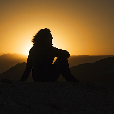Silhouette Of A Woman Sitting With A View Of The Hilly Landscape Of Valle De La Luna At Sunset, San Pedro De Atacama, Antofagasta Region, Chile