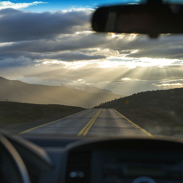 Rays Of Sunlight Shining Through The Clouds Onto The Road As Viewed Through The Windshield Of A Vehicle, Patagonia, Chile