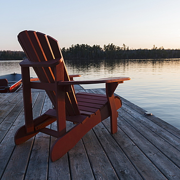 A Red Adirondack Chair Sitting On A Wooden Dock On A Lake At Sunset, Lake Of The Woods, Ontario, Canada