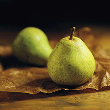 Green Pears Sitting On Brown Parchment Paper On A Wooden Counter, Toronto, Ontario, Canada