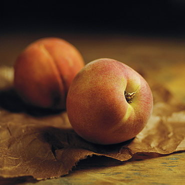 Peaches Sitting On Brown Parchment Paper On A Wooden Counter, Toronto, Ontario, Canada