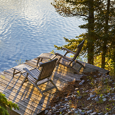 Two Wooden Lounge Chairs On A Dock Looking Out At Lake Of The Woods At Dusk, Ontario, Canada