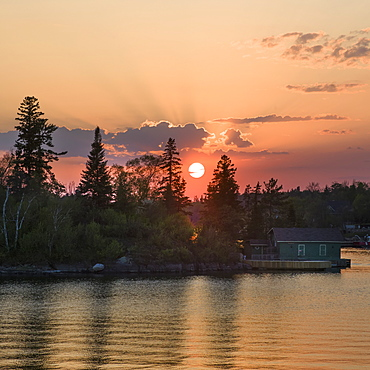 Cottage On The Edge Of A Lake At Sunrise With A Pink Sky, Lake Of The Woods, Kenora, Ontario, Canada