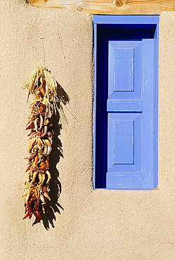 Blue Window And Chili Peppers Hanging On Wall, Taos, New Mexico, Usa