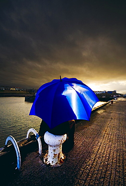 Person With Umbrella In Stormy Skies