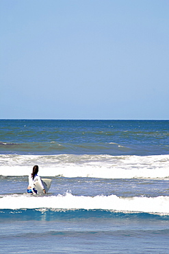 Woman Taking Surfboard Into Sea