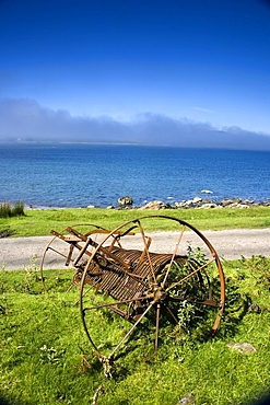 Old Farm Machinery Beside A Road And Lake