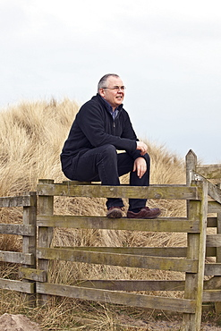 Northumberland, England, A Man Sitting On A Fence