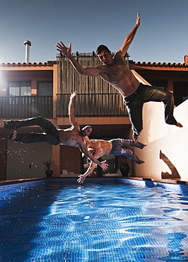 Three Men Jumping Into A Pool Wearing Their Pants, Tarifa, Cadiz, Andalusia, Spain