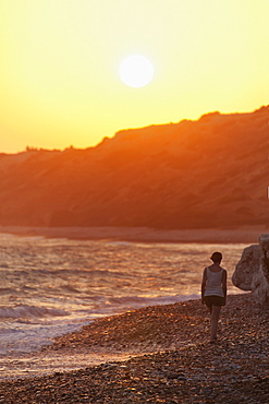 A woman walks along the rock beach at the water's edge at sunset, Aphrodite beach, cyprus